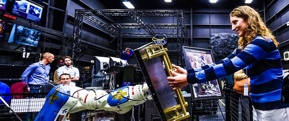 Woman working with robot in science space centre center machine