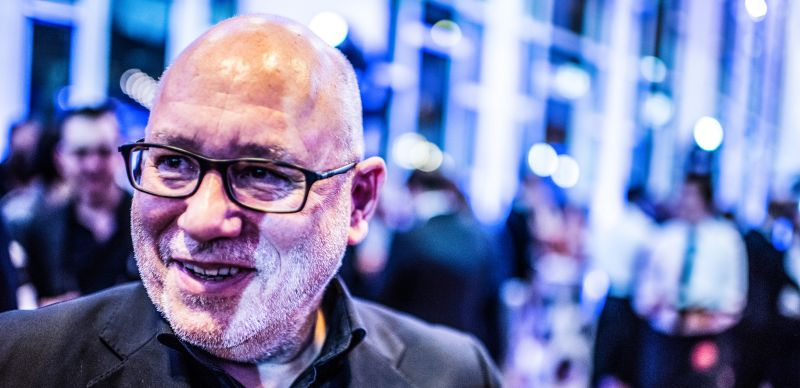 man-bald-beard-smiling-middle-aged-suite-event-laughing-good-mood-influencer-blurry-background