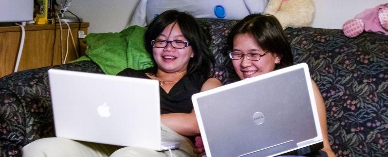 Girls Chatting online IM using Laptops smiling happy cheerful