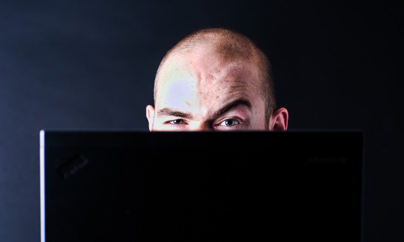Hacker behind Laptop Bald Male Man Working Computer RansomWare WannaCry Encrypted Files Payment