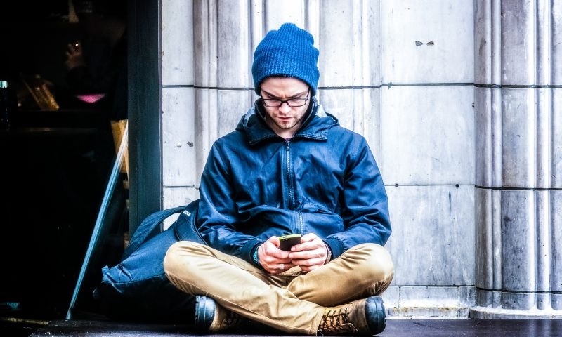 Texting-on-Social-Media-Smartphone-London-UK-Man-Boy-Sitting-Using-Phone.jpg
