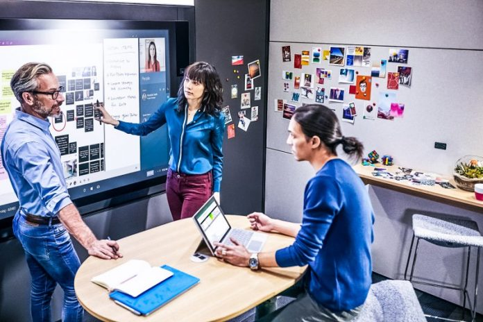 Creative-Spaces-Ideation-Hub-Microsoft-Teams-Design-New-Free-Plan-Costs-Features-Comparison-Matrix-Group-Working-Together-Woman-Man-Brainstorming-Photo-Session