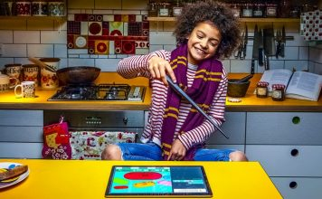 Harry-Potter-Kano-Coding-Wand-STEM-Toys-Learning-Coding-Fun-Education-EdTEch-Child-Sitting-Kitchen-Having-Fun-Young-Scarf-Smiling