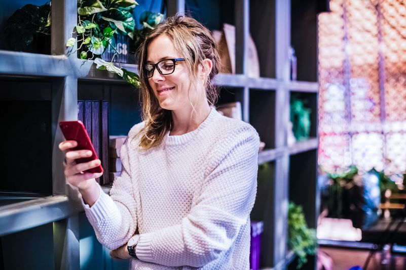 Woman using smartphone social media smiling