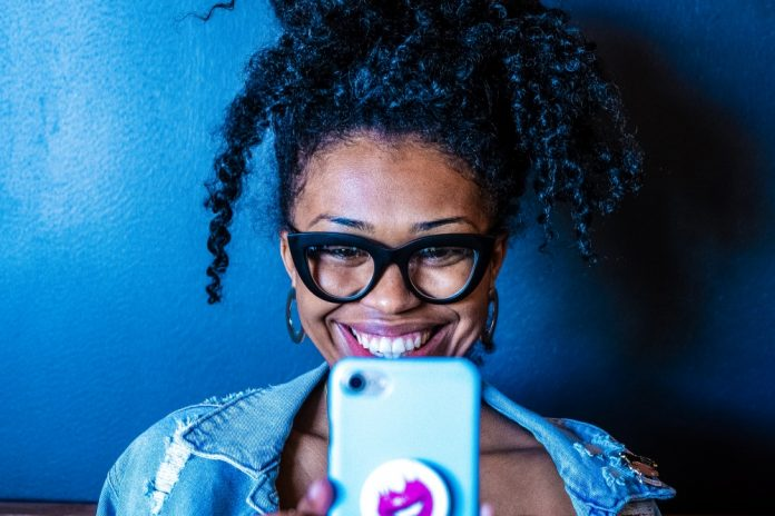 What is eSIM how does an embedded sim card work happy smiling woman using smartphone glasses jeans jacket blue background