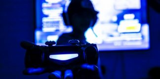 Gaming Accessories Gadgets For Gamers Man Holding PlayStation Controller Blurred Background