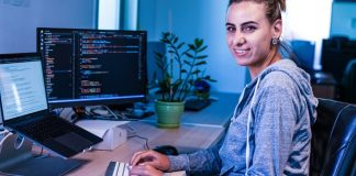 Female-Programmer-Working-Woman-Desk-Keyboard-Smiling-Looking-Laptop-Stand-Coding-Developer-Coder-Office-Ranking-Most-Popular-Programming-Languages